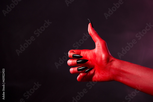 Spooky red devil hand showing thumbs up