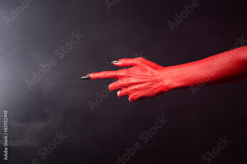 Red devil pointing hand with black sharp nails, extreme body-art