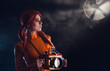 Portrait of sexy astronaut girl in orange latex catsuit
