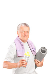 Senior man holding a water bottle and an exercise mat