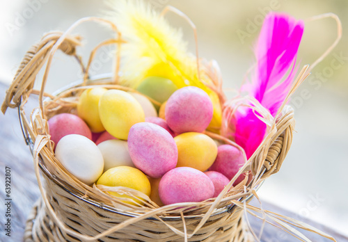 Easter eggs in basket table centerpiece.Marzipan sweets.