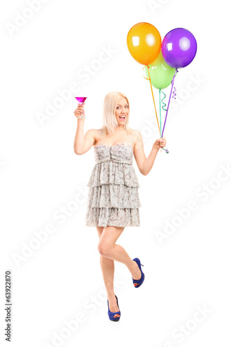 Trendy girl holding a pink cocktail and balloons