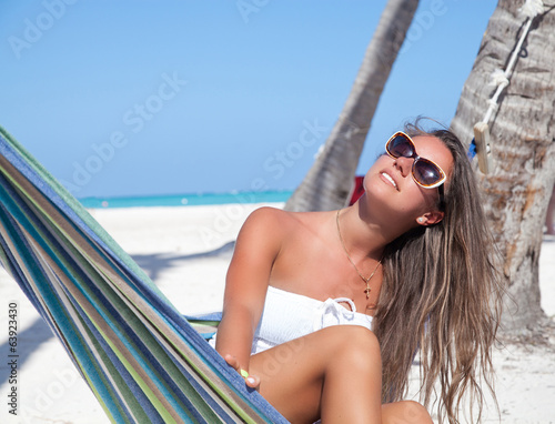 woman relaxing on beach in hammock