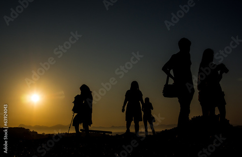 Silhouette of travellers with camera during sunrise on the mount