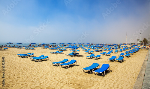 Sunbeds for sunbathing in sunshine, on sand & beach for tourism