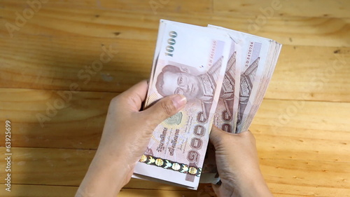 Business woman count Thai money 1000 baht in hands.