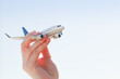 Airplane model in hand on sunny sky. Travel, transportation