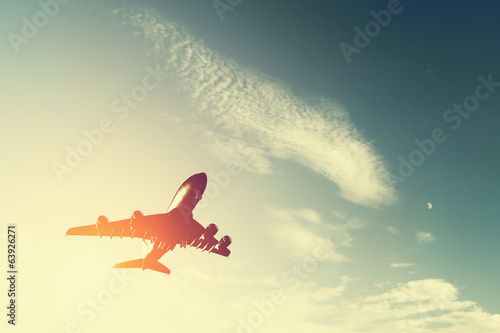 canvas print picture Airplane taking off at sunset. Silhouette of a flying aircraft