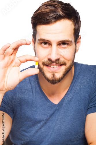 Handsome man showing pills