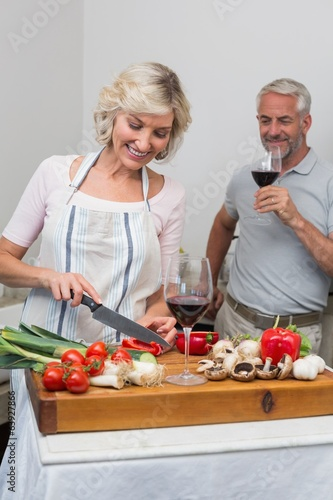 Man with wine glass and woman chopping vegetables in kitchen