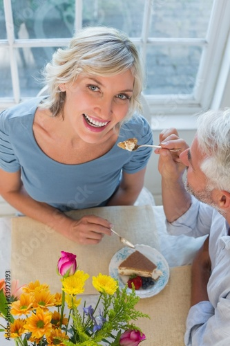 Mature man feeding happy woman pastry