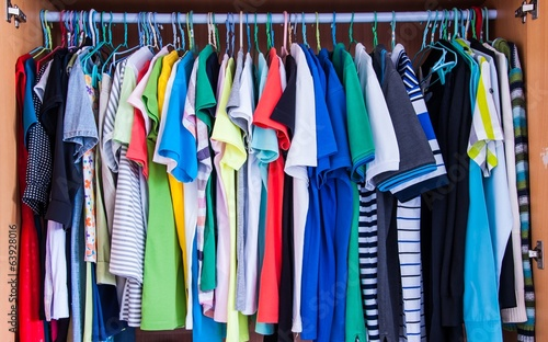 Colorful t-shirts hanging in wardrobe.