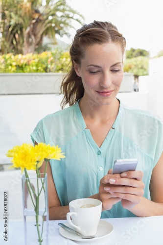 Woman with coffee cup text messaging in café