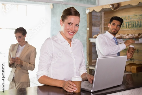 Businesswoman using laptop in office cafeteria