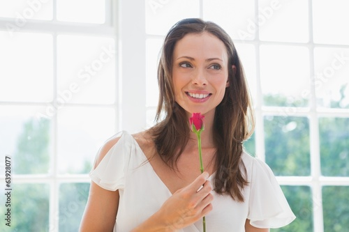 Thoughtful beautiful woman holding flower