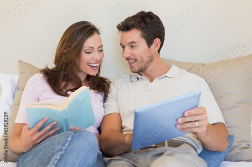 Happy couple with laptop and book on couch