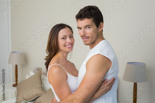 Happy couple with arms around at home