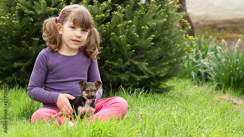 happy little girl play with puppy