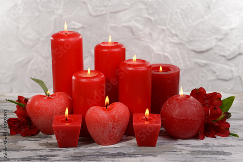 Beautiful candles with flowers on table on grey background