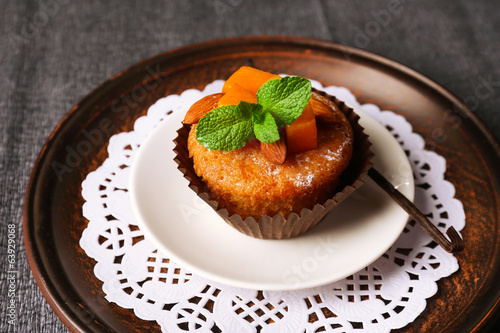 Tasty pumpkin muffin on grey tablecloth