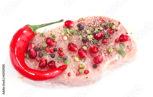 Raw meat steak with herbs, spices and pomegranate seeds,