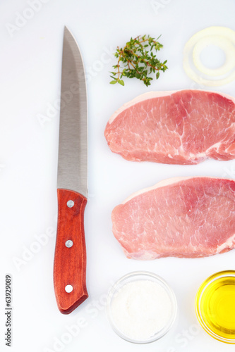 Raw meat, herbs, spices and  knife, isolated white