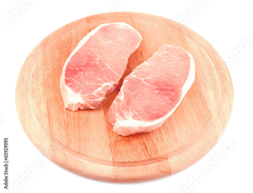 Raw meat steaks on wooden board, isolated on white