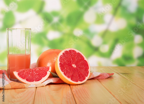 Glass of grapefruit juice and sliced ??on table in yard