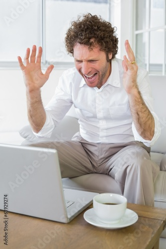 Frustrated man shouting in front of laptop at home