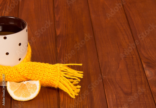 Cup of tea with lemon tied scarf on wooden table background