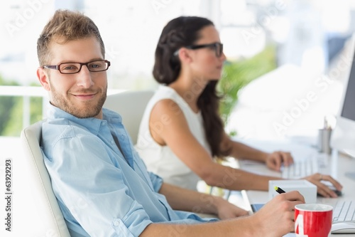 Handsome designer smiling at camera at desk