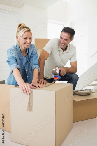 Smiling couple packing boxes in a new house