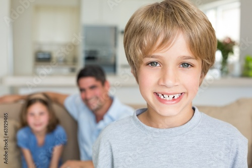 Boy smiling with family in background
