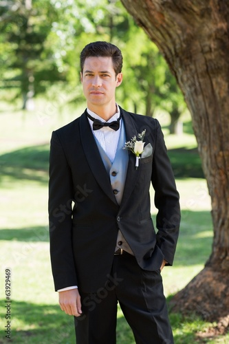 Confident bridegroom in tuxedo at garden