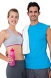 Portrait of a sporty couple with water bottle and towel