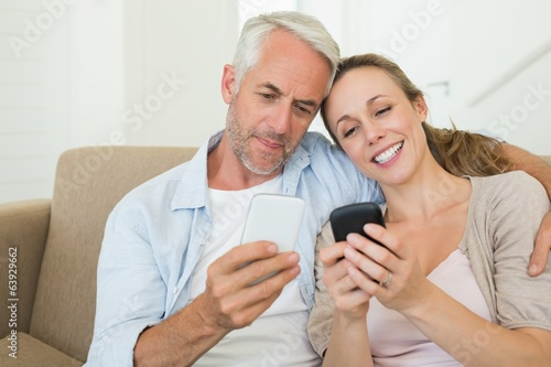 Happy couple sitting on couch texting on their phones