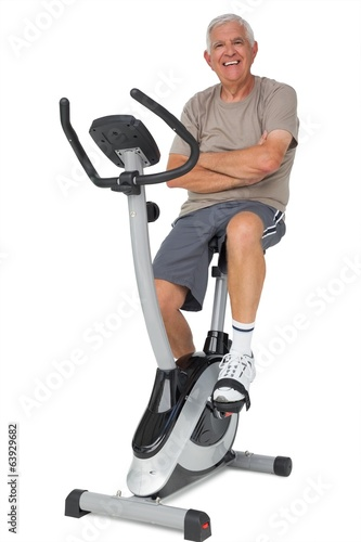Full length portrait of a senior man on stationary bike