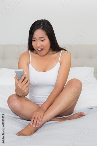 Shocked woman sitting on bed reading a text