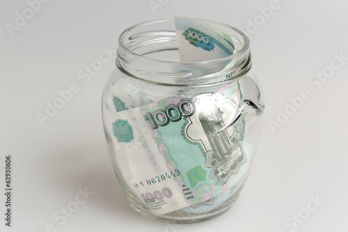 Money in open glass jar on gray background