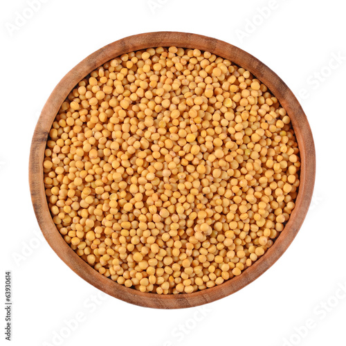 White mustard seeds in a wooden bowl on a white
