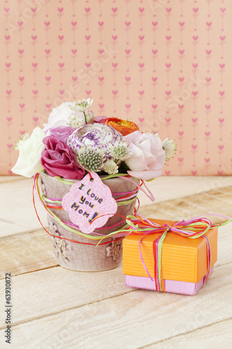 Beautiful bouquet in flowerpot and a gift box for Mother's Day