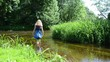 blonde girl long blue mottled dress wade through flowing river