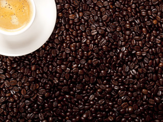 Top view of a cup of dark roasted coffee with coffeebeans