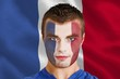 Composite image of serious young france fan with facepaint