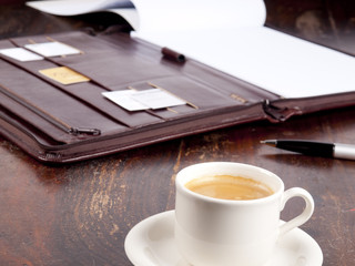 Old fashioned leather folder with a cup of coffee