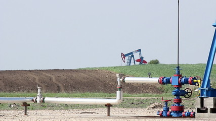 oil pump jack and pipeline close up
