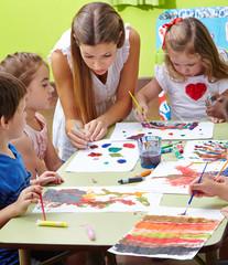 Erzieher und Kinder malen im Kindergarten