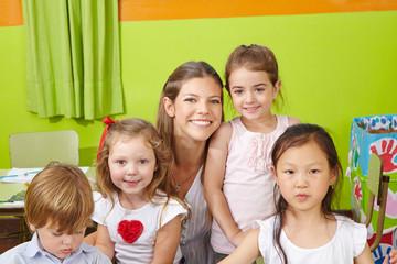 Portrait von Kindern und Erzieherin im Kindergarten