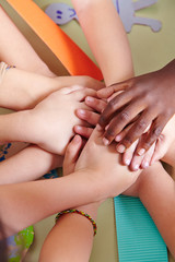 Kinder stapeln Hände im Kindergarten