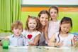 Lachende Frau und Kinder in Kindergarten